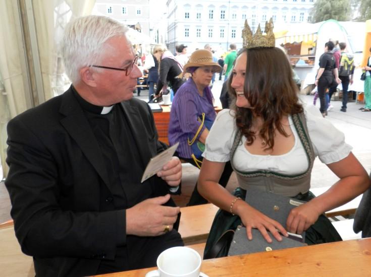 Die Heukönigin schreibt dem Erzbischof eine persönliche Widmung und überreicht ihm ihre Autogrammkarte