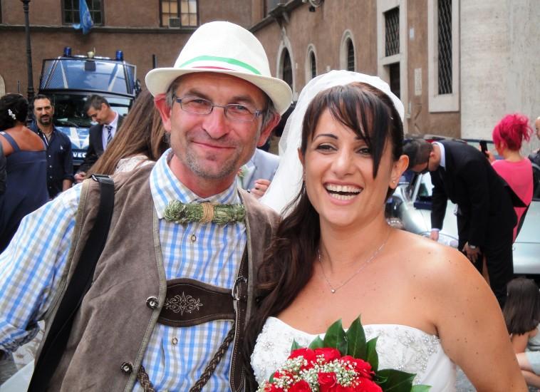 Eine römische Braut mit einem Salzburger in Lederhosen und Heumascherl, welches nach frischem Heu richt
