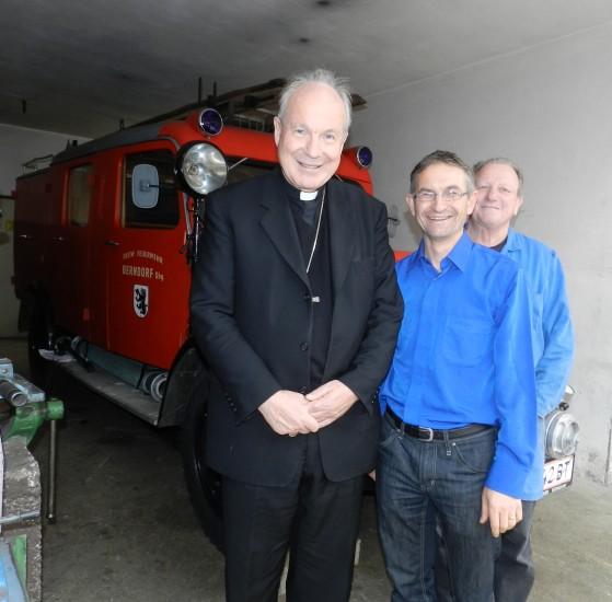 Kardinal Christoph Schönborn vor dem Oldtimer der Feuerwehr Berndorf, welcher gerade zur Reperatur in der Hofwerkstatt stand