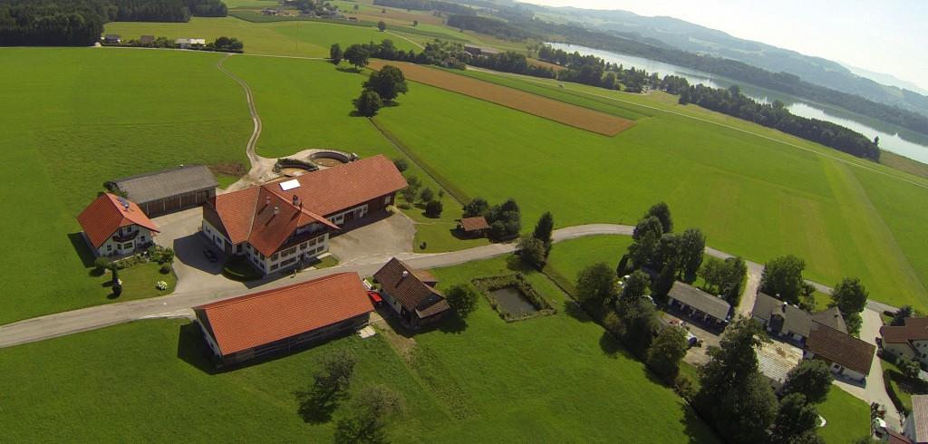 Luftaufnahme unseres Bauernhofes mit dem Grabensee im Hintergrund
