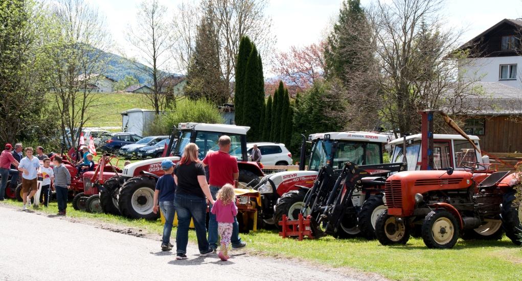Ein Blick auf die andere Strassenseite zeigt unsere Traktoren mit einigen Oldtimern, welche die Kinder begeistertern
